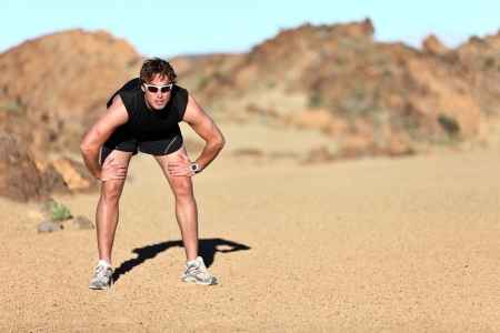 Workout outdoor runner. Man running taking a break from run outside in beautiful desert landscape. Fit young caucausian athletic model training for marathon outdoors. Stock Photo - 12288486