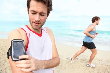 earbud: Running workout man with mp3 music player listening to music with mp3 player armband or smart mobile phone.