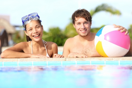 swimming suit: Summer vacation couple having fun in pool on sunny day in tropical resort