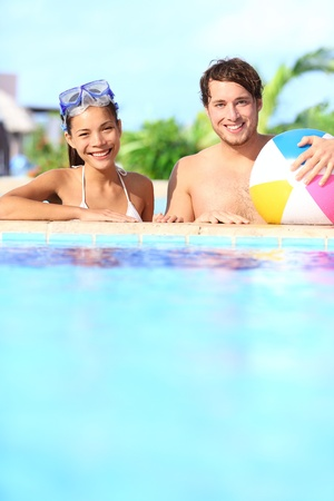 resting mask: Holidays couple in pool having fun in sunny vacation resort under the sun. Young mixed race couple, Caucasian man, Asian woman. Stock Photo