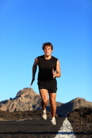 running race: Running - male runner. Man sprinting during outdoor workout training session. Male caucasian athlete running on road in nature.