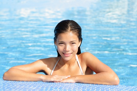 sun bathing: Woman beauty in pool on sunny vacation holiday resort.