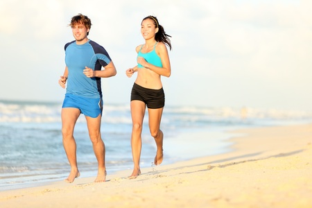 Couple running on beach. Runners jogging during outdoor workout on beautiful beach at sunset. Caucasian man, Asian woman. photo