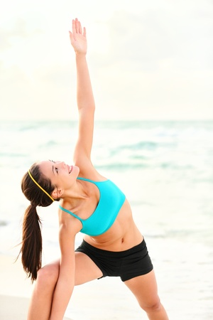 Yoga stretching woman on beach.  photo