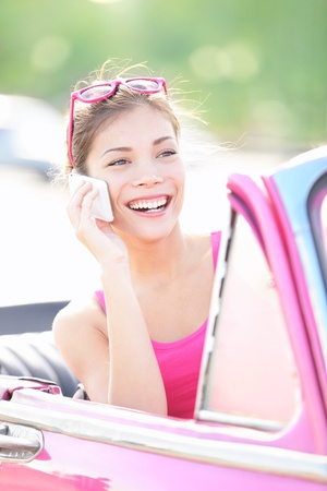 Vintage woman in retro car talking on mobile smart phone. Beautiful young mixed race woman driving in pink car smiling happy. photo