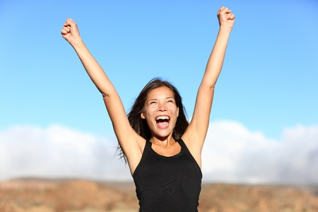 arm raised: Hiker cheering. Woman hiking cheerful with arms stretched screaming of joy on top of mountain. Beautiful sporty mixed ethnicity woman outdoor. Stock Photo