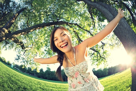 Playful woman in spring having fun in park smiling happy playing joyful. Beautiful young multicultural woman outside on sunny day. photo
