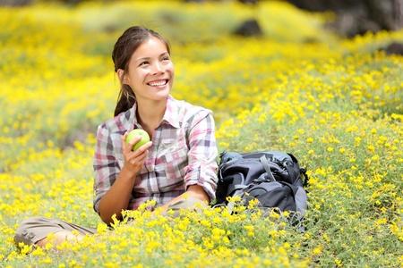 tentempi�: Ni�a de Senderismo en la primavera de flores sentado en el suelo del bosque.