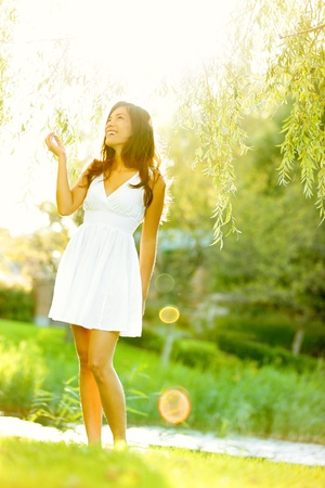 mixed race ethnicity: Spring woman in summer dress walking in park enjoying the sun. Playful and beautiful mixed race girl on warm sunny day.