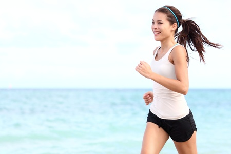 Running woman. Female runner jogging during outdoor workout on beach. Beautiful fit mixed race Fitness model outdoors. Stock Photo