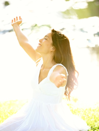stretched: Happy free woman carefree in spring or summer with arms out enjoying the sun joyful in white summer dress sitting in the grass by lake in park.  Stock Photo