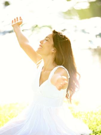 adentro y afuera: Mujer feliz sin preocupaciones en la primavera o el verano con los brazos disfrutando de la alegr�a del sol en vestido de verano blanco, sentado en la hierba al lado del lago en el parque.
