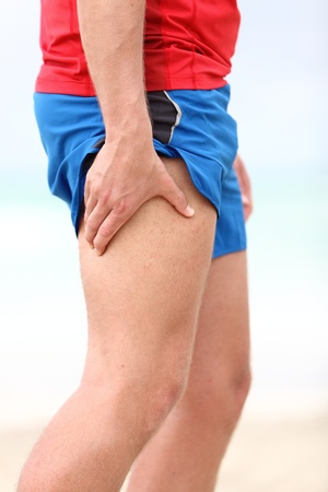 cramps: Muscle sports injury. Running muscle strain injury in thigh. Closeup of runner touching leg in muscle pain.
