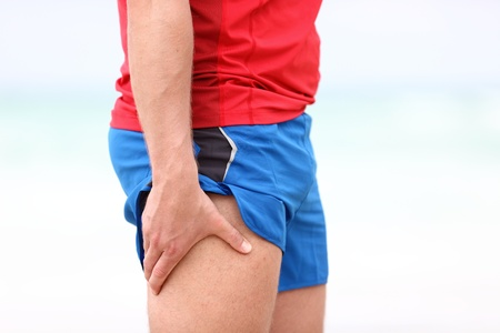 strains: Sports injury. Running muscle stain injury in thigh. Closeup of runner touching leg in muscle pain. Stock Photo