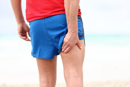 Running sports injury. Pulled muscle, muscle strain or muscle cramp in back thigh leg of man running outdoors. photo