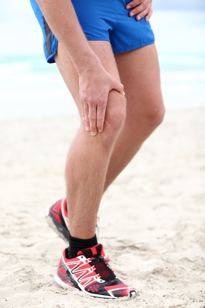 Knee pain - runner injury. Pain in knee joints in man running on beach. photo