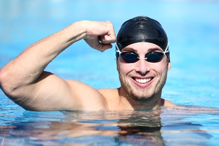 winning race: Sport swimmer winning  Man swimming cheering celebrating victory success smiling happy in pool wearing swim goggles and black swimming cap  Caucasian male fit fitness model  Stock Photo