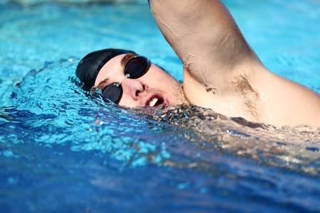 axila: El hombre de nataci�n estilo libre masculino rastreo rastreo nadador haciendo rastreo de nataci�n en la piscina de accidente cerebrovascular usando gafas de nataci�n y gorro de ba�o masculino cauc�sico modelo de la aptitud deportiva Foto de archivo