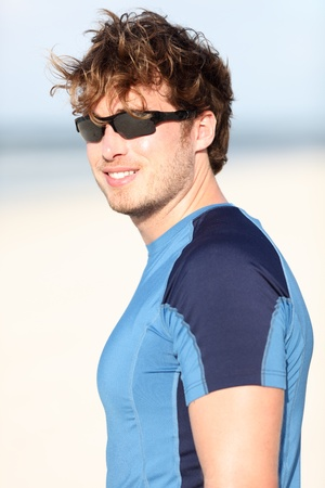 Sporty young man on beach smiling happy after outdoor running workout Caucasian male fitness model outside