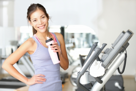 Gym woman working out drinking water smiling happy standing by moonwalker fitness machines. Beautiful fit young mixed race Caucasian  Chinese Asian female fitness model inside in fitness center.