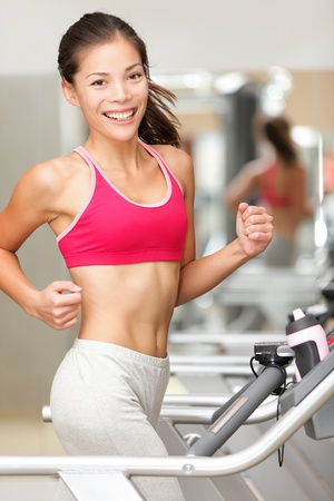 Woman running on treadmill in gym. Fitness model jogging indoors in health club smiling happy. Beautiful young mixed race female model of Chinese Asian and Caucasian ethnicity. photo