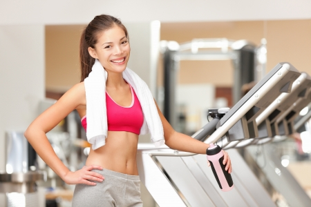 cardio fitness: Fitness woman in gym. Portrait of fit workout girl with towel standing by treadmills in fitness club. Happy smiling young multicultural fitness model. Stock Photo