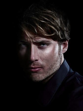 Man - portrait beauté masculine sur fond noir. Jeune homme de race blanche regardant de près grave.