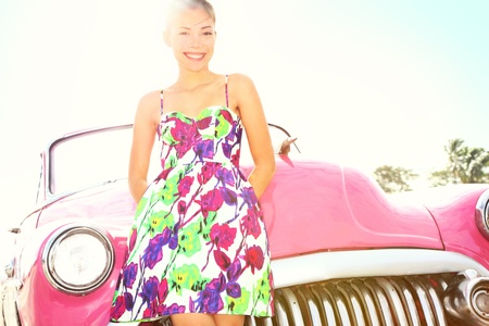 Vintage woman and car. Old retro style car and beautiful young happy smiling woman on road trip. Pretty mixed race Caucasian  Asian Chinese female lifestyle model. Photo from Havana, Cuba. photo