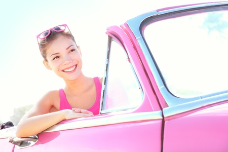 woman driving: Woman driving vintage car. Retro style image of happy smiling young woman in old pink car going on road trip on sunny spring or summer day. Beautiful multiracial Caucasian  Chinese Asian lifestyle model outdoor. Photo from Havana, Cuba. Stock Photo