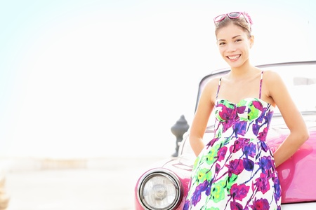 drivers: Car woman smiling happy standing in front of pink retro vintage car. Portrait of pretty girl in summer dress.  Multicultural Chinese Asian  Caucasian female lifestyle model. Photo from Havana, Cuba.