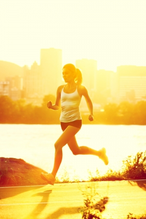 runners - woman running outdoors in sunshine. Young woman jogging in city of Montreal, Quebec, Canada, photo