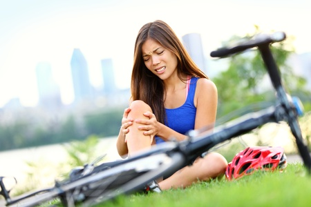 Knee pain bike injury. Woman with pain in knee joints after biking on bicycle. Girl sitting down with painful face expression. Mixed race sport fitness model outdoors. Stock Photo