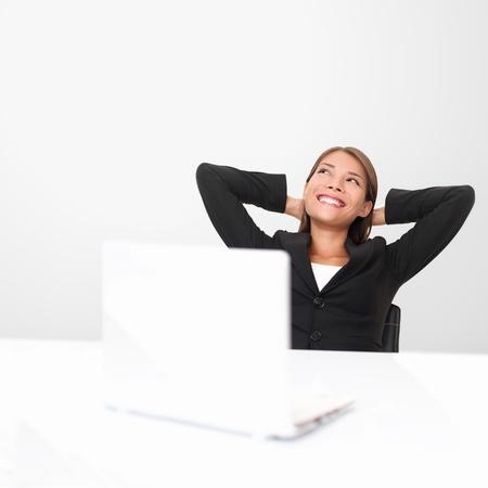 so�ando: Pensando en los trabajadores de oficina so�ar despierto mirando sonriendo feliz. Joven mujer de negocios en traje sentado en el escritorio de oficina con ordenador port�til. Joven empresaria de raza mixta asi�tica  cauc�sica.