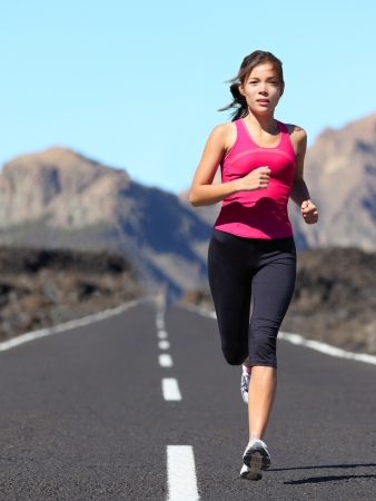 Jogging woman running. Female runner during outdoor workout in beautiful mountain nature landscape. Beautiful young mixed race fit fitness model training for marathon. photo