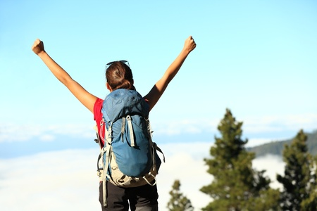 reached: Success. Successful happy hiker cheering having reached summit and goal. Young woman hiking in mountain nature joyful.