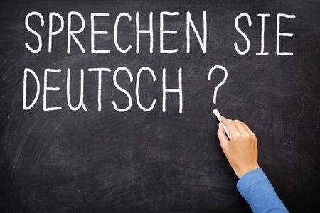 Learning language - German  Sprechen Sie Deutch  Do you speak German  written on blackboard  German language class concept showing teacher hand writing in German on chalkboard  Stock Photo