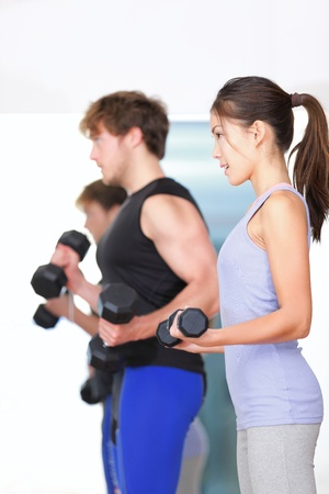 Fitness people in gym Couple strength training lifting weights during indoor fitness workout Woman lifting dumbbells training biceps in focus