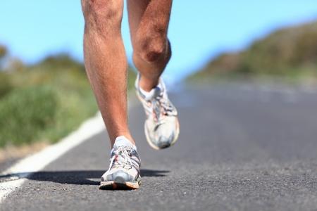 cross leg: - El calzado para correr las piernas del corredor y close-up zapatilla de trotar al aire libre del hombre en la carretera