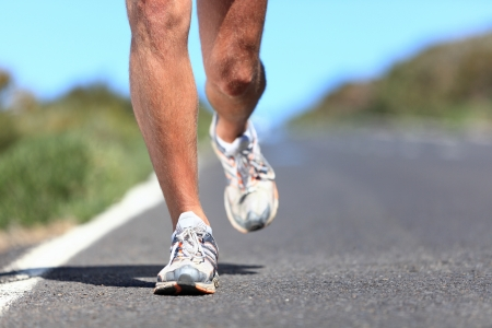 mens: Running shoes - runner legs and running shoe closeup of man jogging outdoors on road