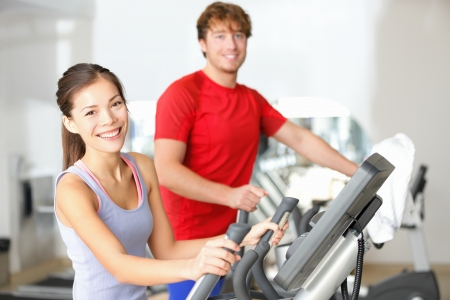 men exercising: Fitness center people smiling happy working out on moonwalker fitness machines in fitness center  Asian woman, Caucasian man