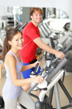 Gym people in fitness center doing walking workout on moonwalker fitness machines  Young couple, asian girl and caucasian man training in gym smiling happy  photo