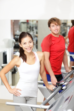 Fitness people  Couple running on treadmill indoors in gym fitness center  Young woman fitness model smiling with young man behind  photo