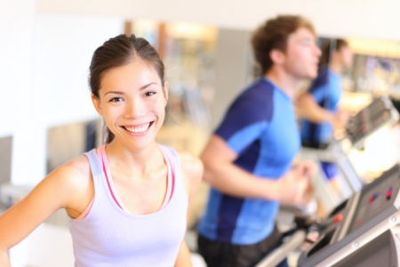 Fitness people portrait in gym  Woman smiling happy during running workout on treadmill in fitness center  Mixed race Cauasian   Chinese Asian female fitness model  photo