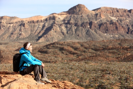 Hiking - woman hiker enjoying view  Woman sitting looking over beautiful volcano mountain landscape  From volcano Teide, Tenerife, Canary Islands, Spain  photo