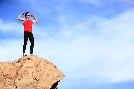 Success - winner man on mountain top celebrating showing muscles in sporty outfit  Fit caucasian male fitness model cheering on top of the world  photo