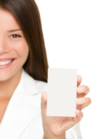 Woman showing business card. Businesswoman in suit holding blank card sign. Can be replaced with mobile phone or smart phone. Mixed race Asian  Caucasian business woman on white background in suit. photo