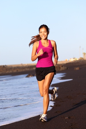Fitness sport woman running on beach outside at sunset. Healthy lifestyle image of beautiful young asian woman jogging on black sand beach. photo