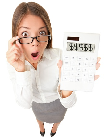 Business woman accountant shocked showing dollar signs on calculator. Surplus, debt or financial crisis concept image. Funny surprised young woman isolated on white background in high angle view.