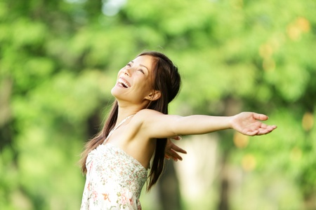 aspirational: Happy woman in spring  summer smiling carefree and joyful in summer dress in beautiful park. Aspirational freedom concept with beautiful mixed race asian  caucasian girl Stock Photo