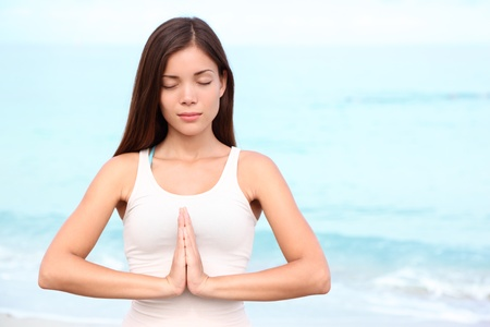 mujer meditando: Yoga meditación mujer. Meditando joven mujer asiática que hace yoga en la playa. Hermosa serena raza mixta chino asiático  caucásico modelo de fitness femenino se relaja en la playa. Foto de archivo